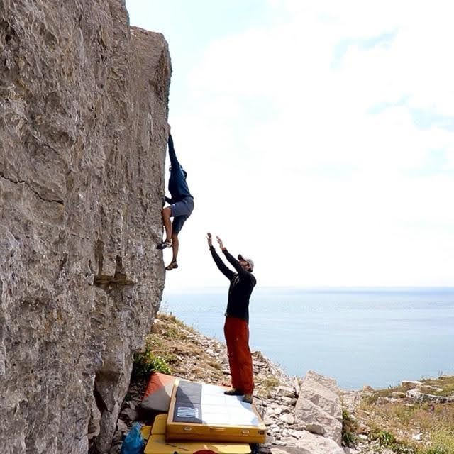 Brett Ffinch and Sophie Cheng from the Climbing Nomads bouldering outdoors by the sea