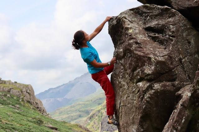 Sophie Cheng from the Climbing Nomads reaching the top of a boulder outdoors