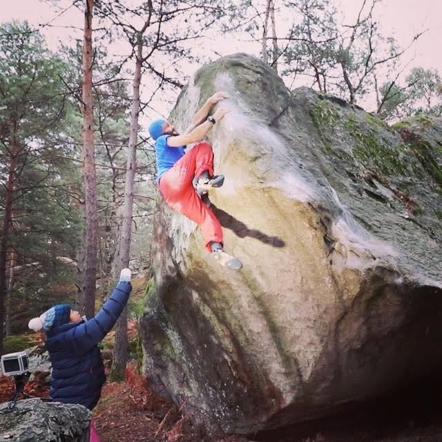 Brett Ffinch from the Climbing Nomads bouldering outdoors while Sophie Cheng spots him