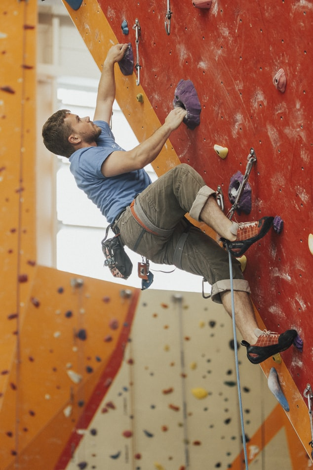 male sport climber at an indoor climbing gym